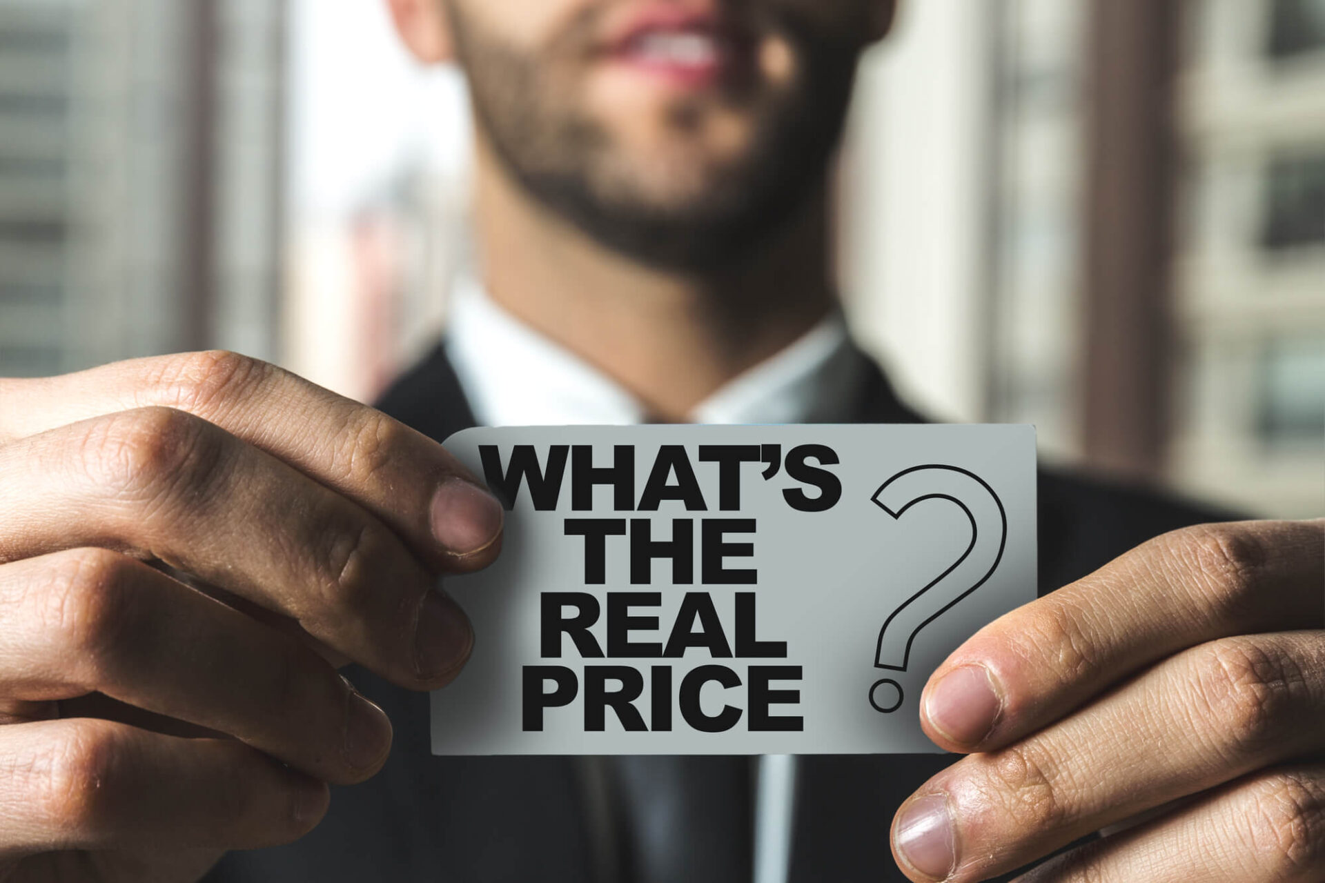 Man holding Card with question: what's the real price?