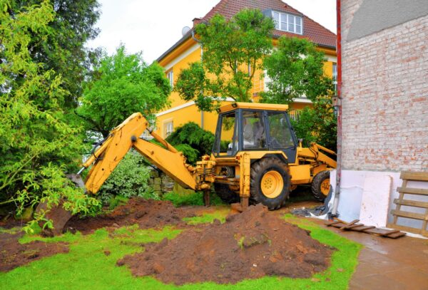 Excavator digging up the back lawn of a residential property to access underground drain, sewer or stormwater pipes.